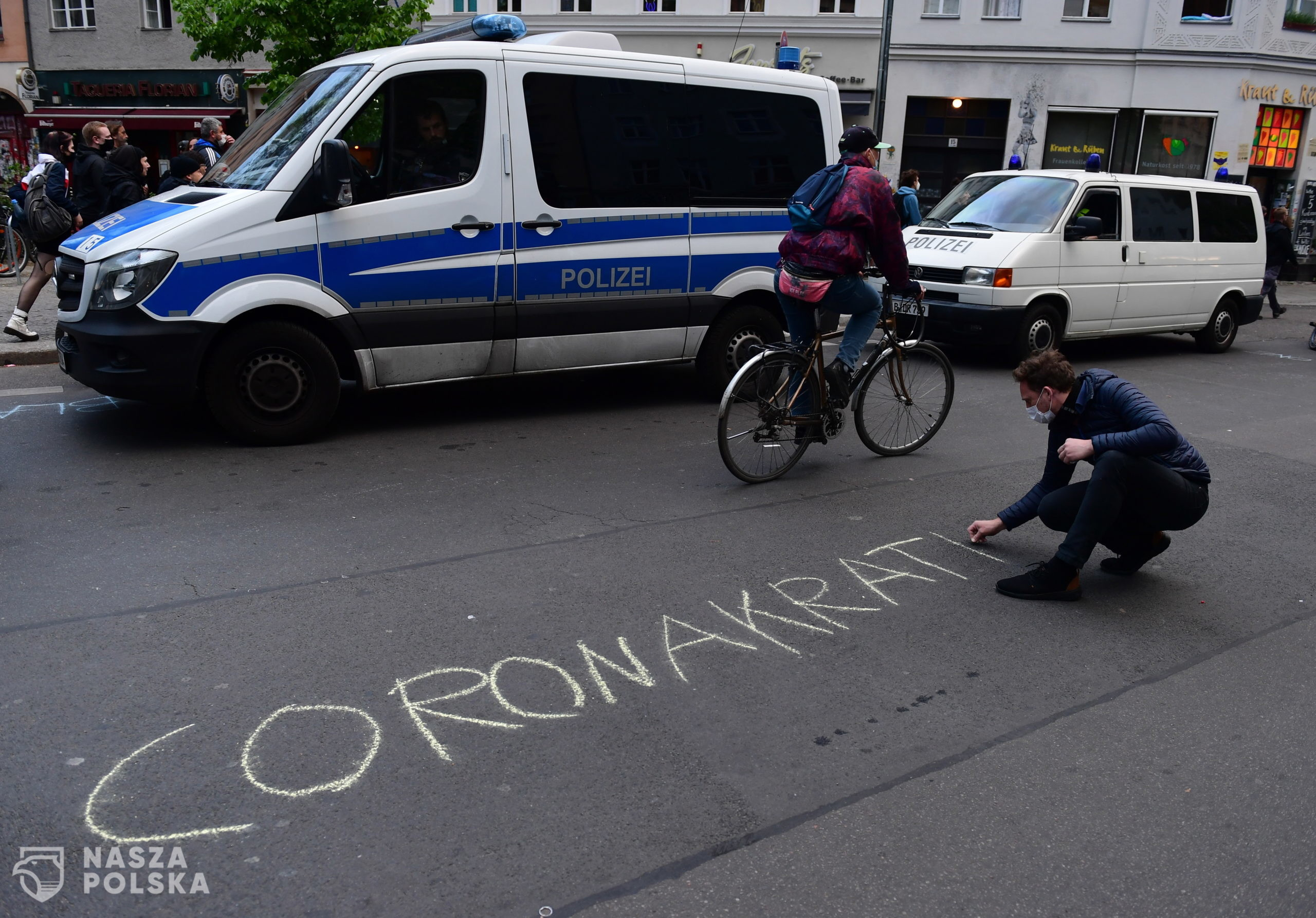 epa08396696 A man writes 'Coronacracy' on a street during a protest on May Day in the district Kreuzberg in Berlin, Germany, 01 May 2020. Labour Day, or May Day, is observed all over the world on the first day of May to celebrate the economic and social achievements of workers and fight for labourers rights. This year, May Day takes place under the influence of the pandemic crisis of the SARS-CoV-2 coronavirus which causes the Covid-19 disease.  EPA/FILIP SINGER  Dostawca: PAP/EPA.