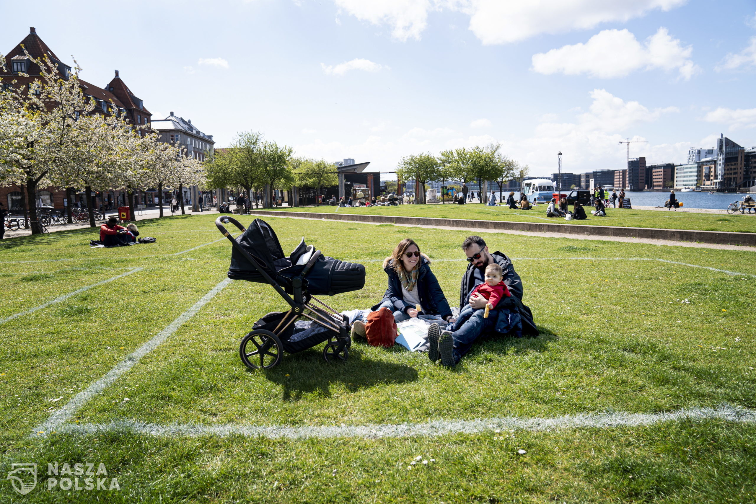 epa08398885 Marina and Andrea enjoy the sun with their daughter Sara at Islands Brygge in Copenhagen, Denmark, 03 May 2020. Marked areas of 40 m2 in which only 10 people can stay, will help citizens keep distance to prevent the spread of SARS-CoV-2 coronavirus which causes the Covid-19 disease. The green area is a favorite place of leisure activities for the residents of Islands Brygge.  EPA/IDA GULDBAEK ARENTSEN  DENMARK OUT  ** NOTE the picture taken with a telephoto lens and the distance between people in the picture can be perceived less than it really is. **  Dostawca: PAP/EPA.