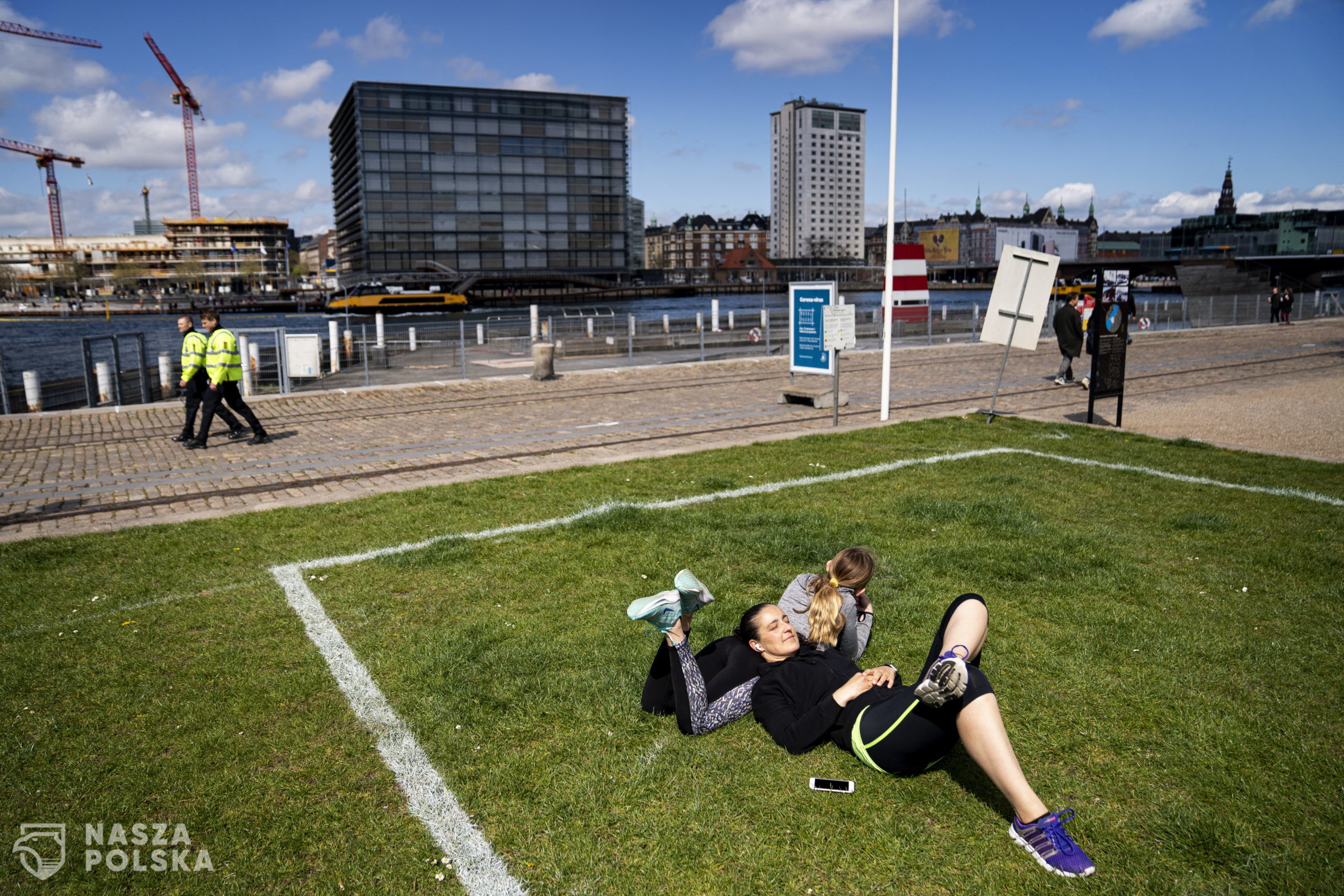 epa08398886 Livia and Lorenza enjoy the sun at Islands Brygge in Copenhagen, Denmark, 03 May 2020. Marked areas of 40 m2 in which only 10 people can stay, will help citizens keep distance to prevent the spread of SARS-CoV-2 coronavirus which causes the Covid-19 disease. The green area is a favorite place of leisure activities for the residents of Islands Brygge.  EPA/IDA GULDBAEK ARENTSEN  DENMARK OUT  ** NOTE the picture taken with a telephoto lens and the distance between people in the picture can be perceived less than it really is. **  Dostawca: PAP/EPA.