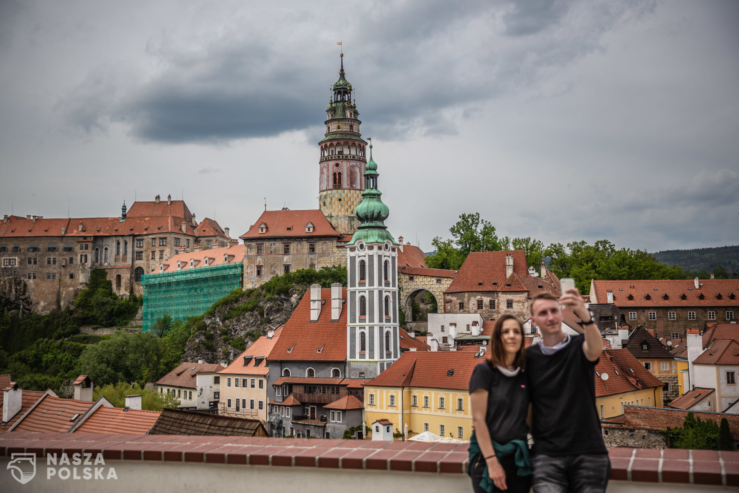 epa08438217 A couple takes selfie at almost empty vantage point above the old town of Cesky Krumlov, UNESCO World Culture Heritage site, Czech Republic, 22 May 2020. According to local media, more than 15.000 tourists from Asia arrived in the South Bohemian region, where is located the popular tourist destination Cesky Krumlov, on January 2020. Due to the pandemic COVID-19 disease caused by the SARS-CoV-2 coronavirus, which closed borders and restricted travel, the number of accommodated tourists in southern Bohemia fell by 30 percent in the first quarter. The region is the most affected in the country.  EPA/MARTIN DIVISEK  Dostawca: PAP/EPA.