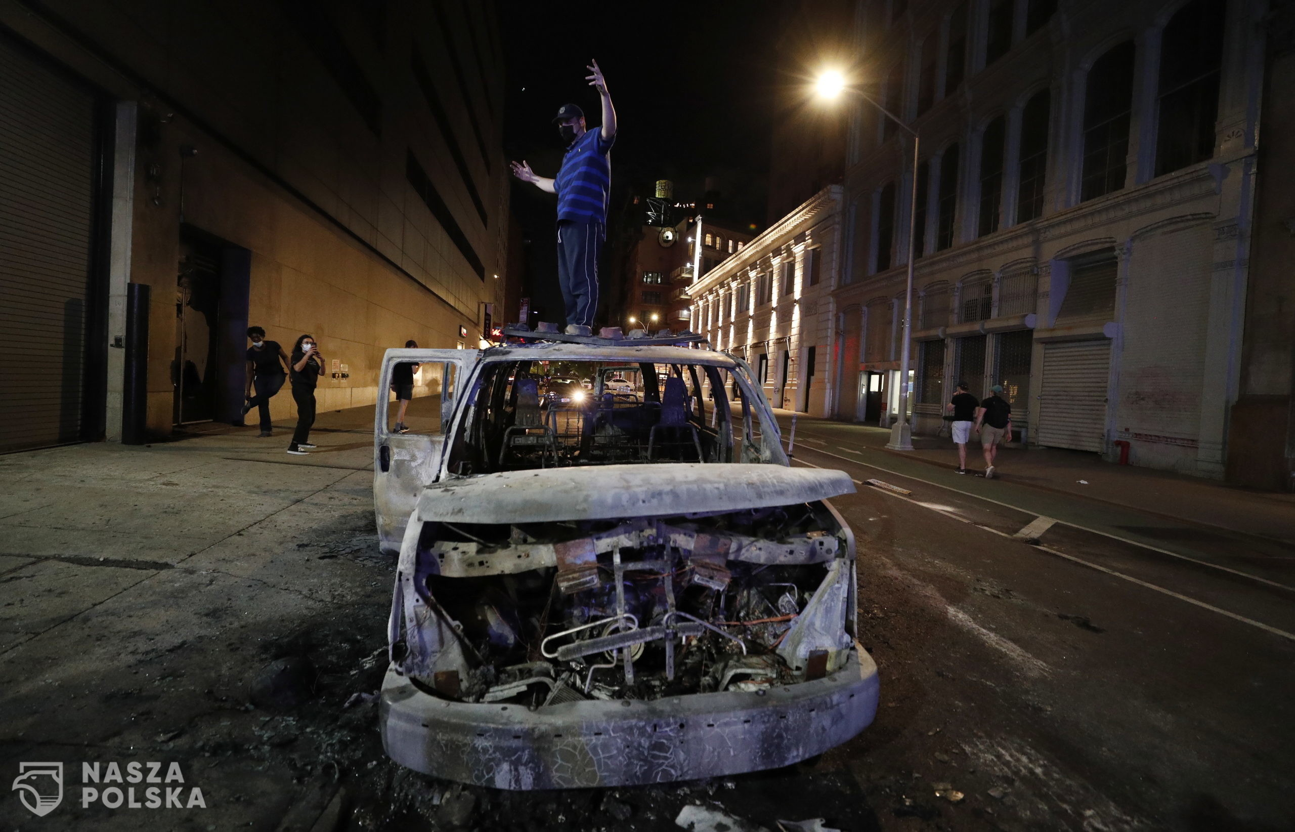 epa08455449 A protester stands on a burned out New York City Police Department vehicle a protesters demostrate about the arrest of George Floyd, who later died in police custody, in New York , New York, USA, 30 May 2020. A bystander's video posted online on 25 May, appeared to show George Floyd, 46, pleading with arresting officers that he couldn't breathe as an officer knelt on his neck. The unarmed black man later died in police custody.  EPA/JUSTIN LANE  Dostawca: PAP/EPA.