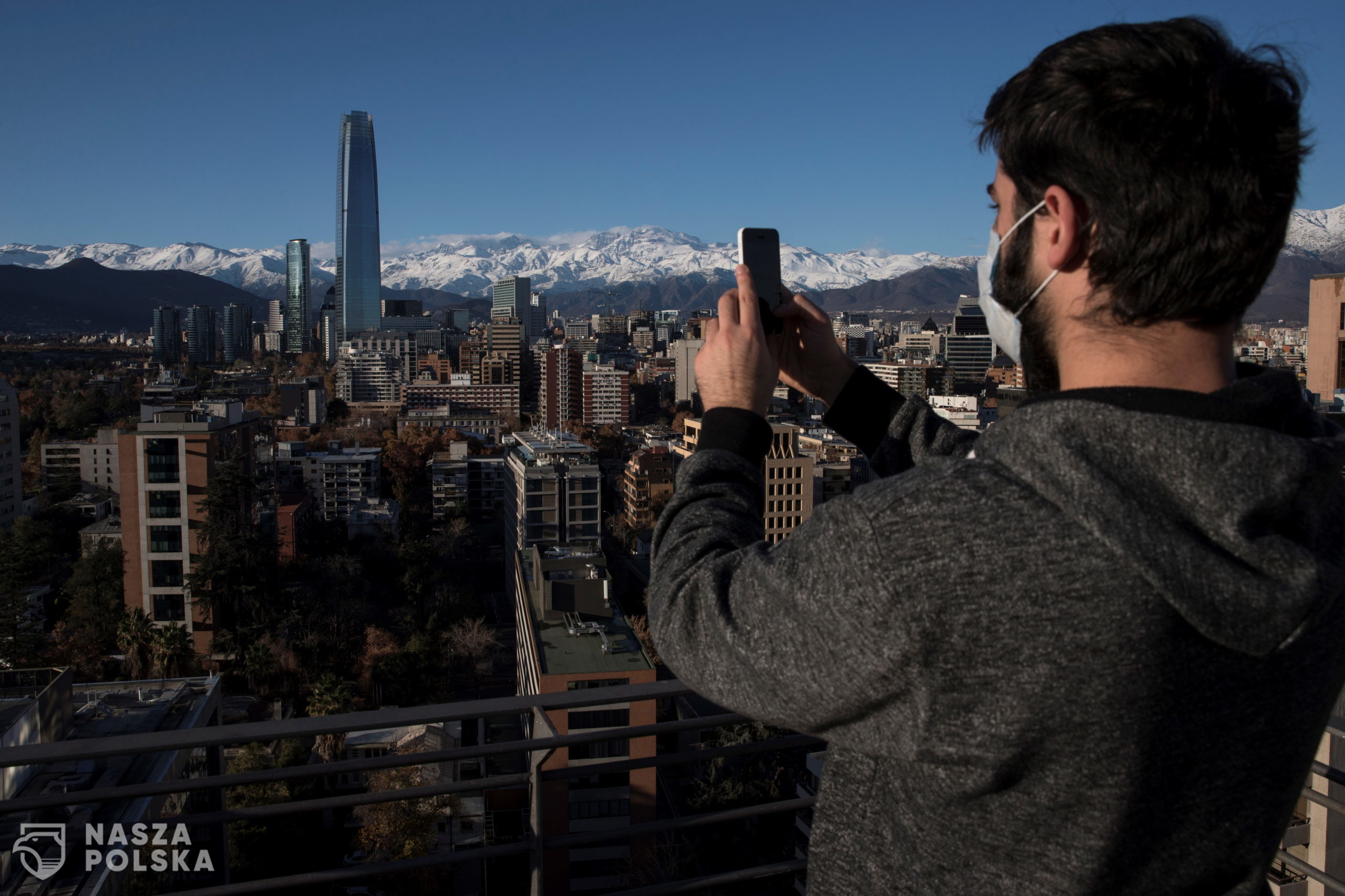 epa08481824 A man takes a picture of the Andes mount range overlooking Santiago, Chile, 12 June 2020.  EPA/Alberto Valdes  Dostawca: PAP/EPA.