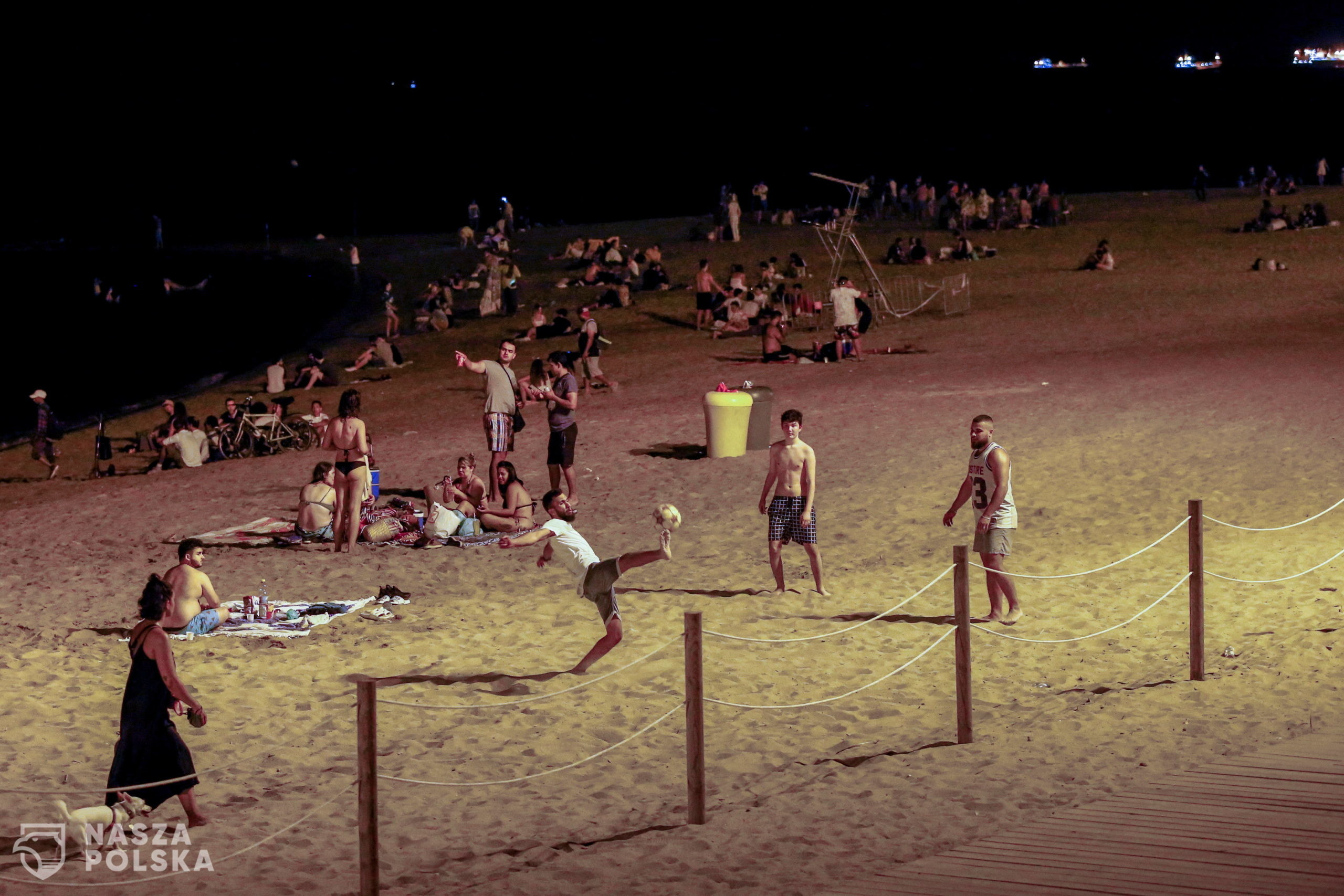 epa08566529 Youngsters are seen at the beach in Barcelona, Spain, early 26 July 2020, after night clubs all over the region shut down ordered by the Catalan Government. A new outbreak in various parts of Catalonia with a high number of young people testing pisitive, has taken the Government to take this decision that night Clubs have already announced they will be talking to court as they assure this measure is not 'justified'.  EPA/Quique Garcia  Dostawca: PAP/EPA.