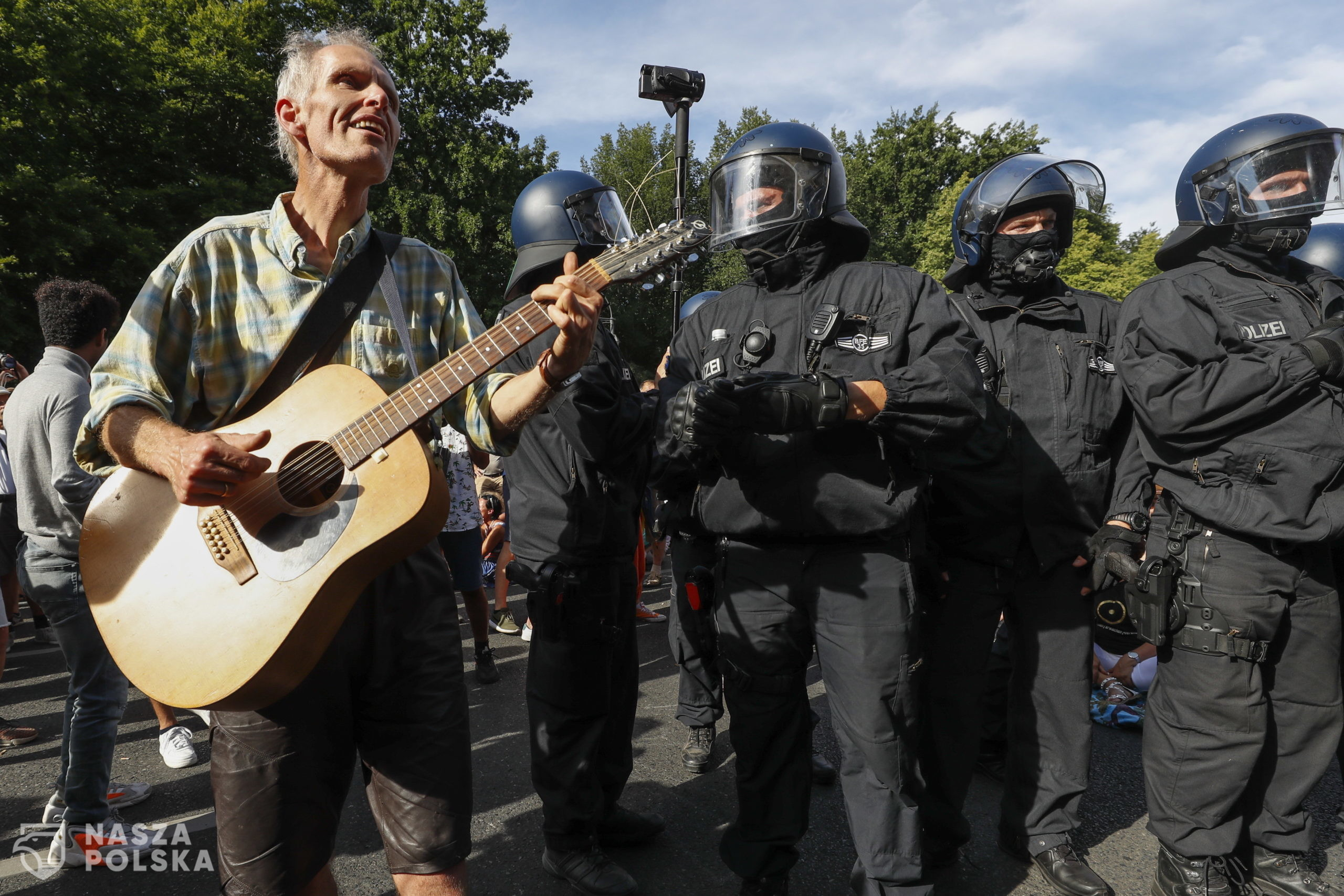 epa08579074 A demonstrator plays on a guitar in front of policemen during a protest against coronavirus pandemic regulations in Berlin, Germany, 01 August 2020. An alliance of right wing groups have called to a democratic resistance demonstration for the first weekend in August. The nationwide rally 'Day of Freedom' will take place 01 August as a protest against the measures imposed by the Government in relation to the coronavirus pandemic. The events are organized by groups of various motives, right wing activists, conspiracy theory believers and more.  EPA/FELIPE TRUEBA  Dostawca: PAP/EPA.