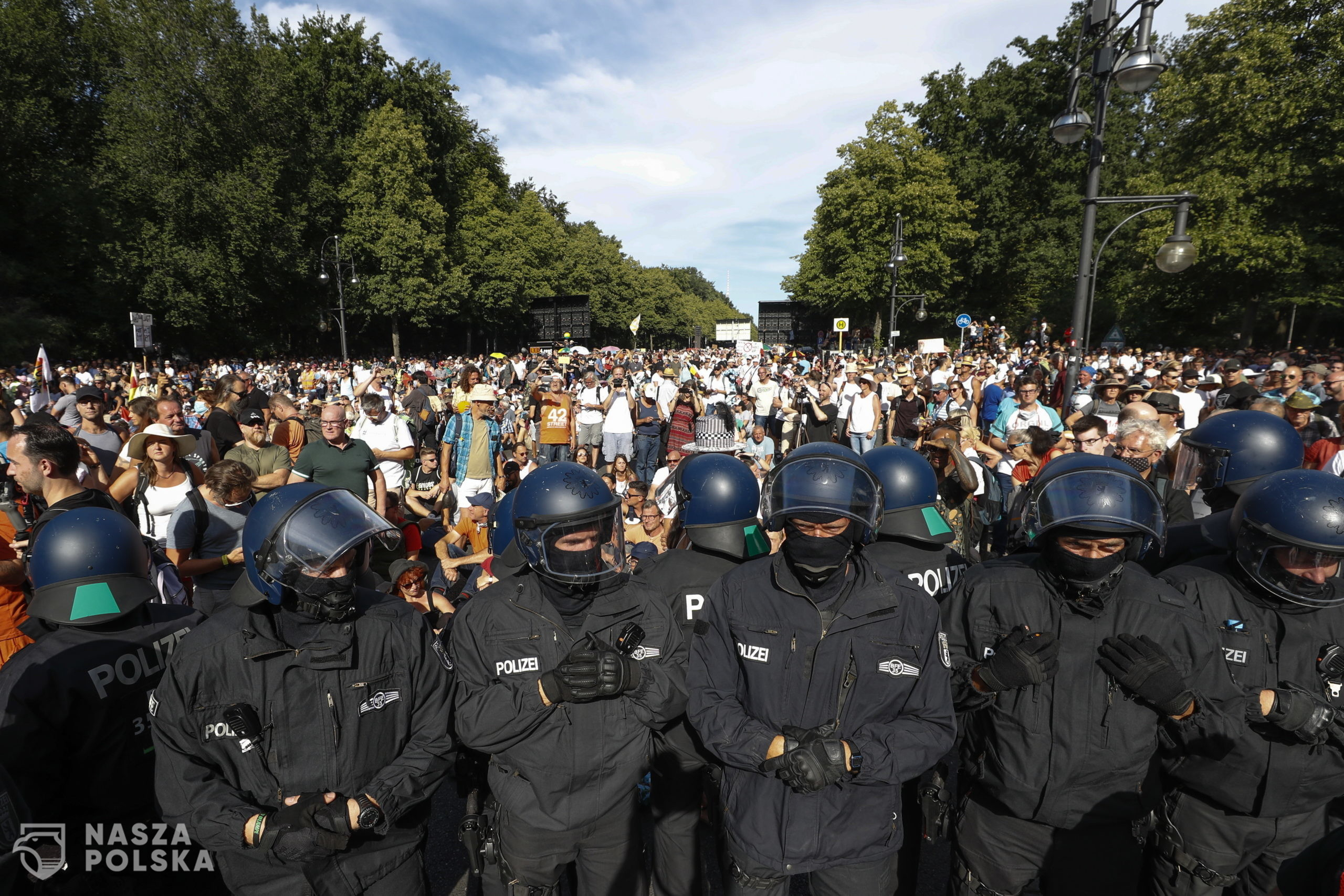 epa08579075 Police form a row in front of demonstrators during a protest against coronavirus pandemic regulations in Berlin, Germany, 01 August 2020. An alliance of right wing groups have called to a democratic resistance demonstration for the first weekend in August. The nationwide rally 'Day of Freedom' will take place 01 August as a protest against the measures imposed by the Government in relation to the coronavirus pandemic. The events are organized by groups of various motives, right wing activists, conspiracy theory believers and more.  EPA/FELIPE TRUEBA  Dostawca: PAP/EPA.