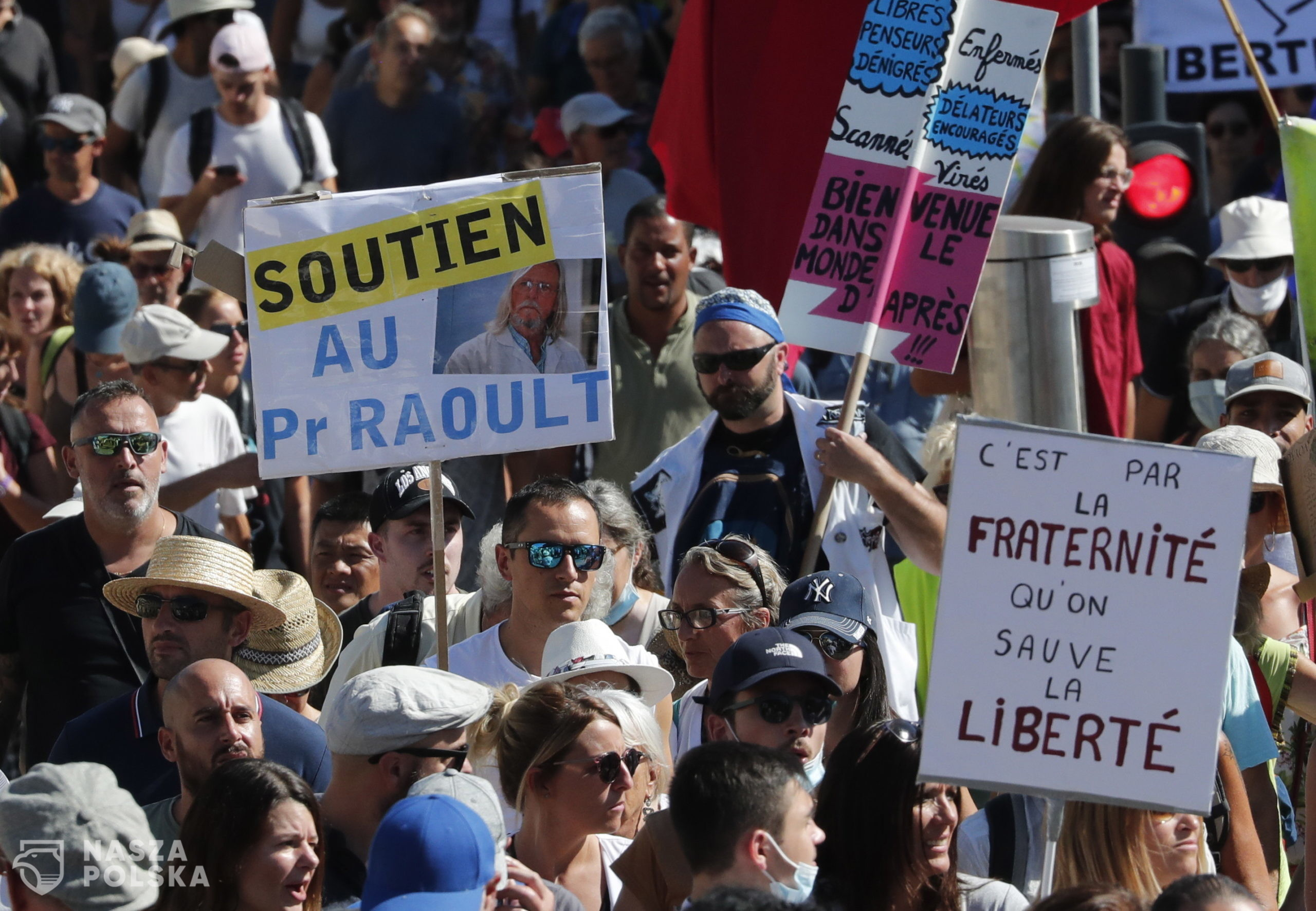 epa09434176 Protesters hold a poster reading 'Support professor Raoult' during a demonstration against the COVID-19 sanitary pass, which grants vaccinated individuals greater ease of access to venues, in Montpellier, France, 28 August 2021. For the seventh consecutive week, thousands of French demonstrators have taken to the streets in several cities across the country to protest against measures to curb the spread of coronavirus.  EPA/GUILLAUME HORCAJUELO  Dostawca: PAP/EPA.